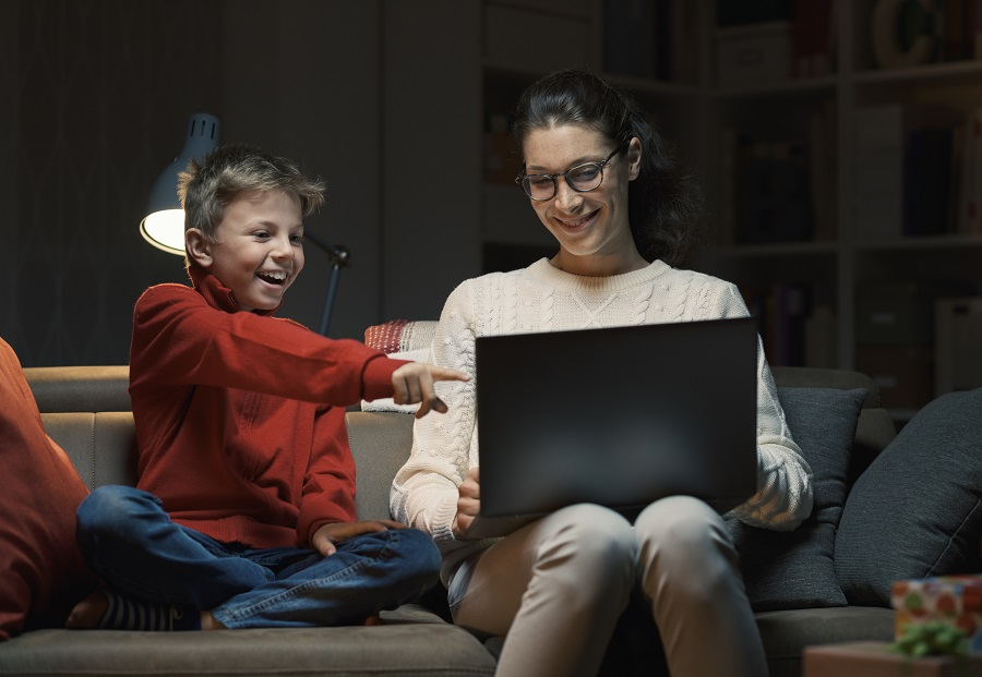 Happy mother and son relaxing together at home, they are sitting on the sofa and watching movies on the laptop